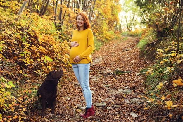 Mooie zwangere vrouw op een wandeling met de hond in de herfst. zwangerschap en huisdieren.