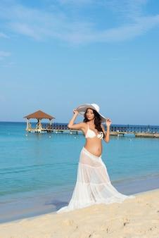 Mooie zwangere vrouw op een zandstrand. dominicaanse republiek, de caribische zee.