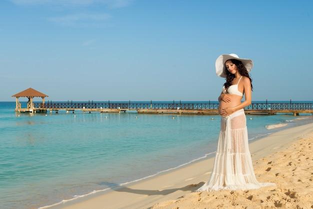 Mooie zwangere vrouw op een zandstrand haar buik knuffelen. dominicaanse republiek, de caribische zee.