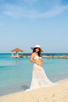 Mooie zwangere vrouw op een zandstrand maakt een hart op de achtergrond van de buik dominicaanse republiek, de caribische zee