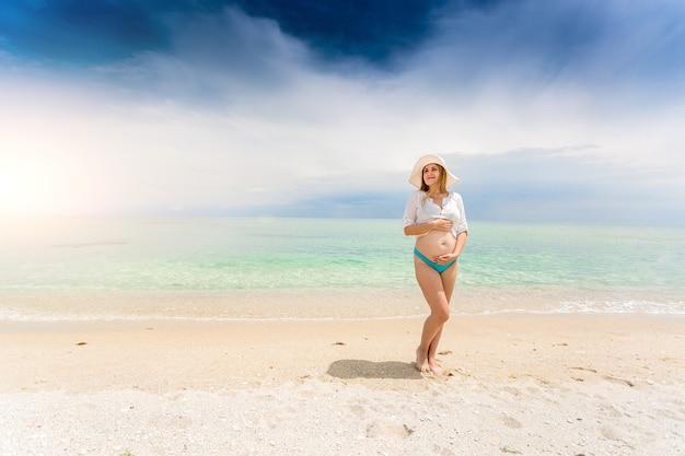 Mooie zwangere vrouw poseren aan de kust en hand in hand op de buik