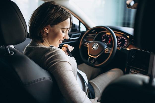 Mooie zwangere vrouw rijden in de auto