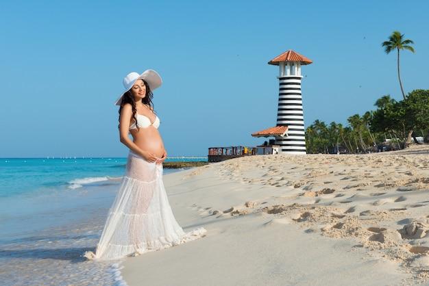 Mooie zwangere vrouw staande op een zandstrand met palmbomen op de achtergrond van een vuurtoren. dominicaanse republiek, caribische zee