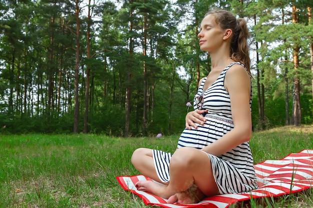 Mooie zwangere vrouw zittend op het gazon met gras op de mat en mediteren met gesloten ogen