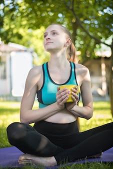 Mooie zwangere vrouwen die op yogamat met kop thee zitten. zomerochtend in de tuin.
