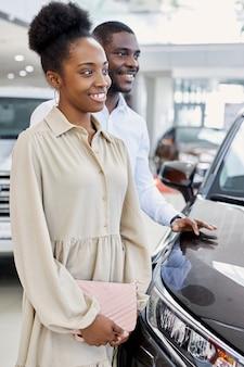 Mooie zwarte afro paar aandachtig luisteren naar consultant in dealer