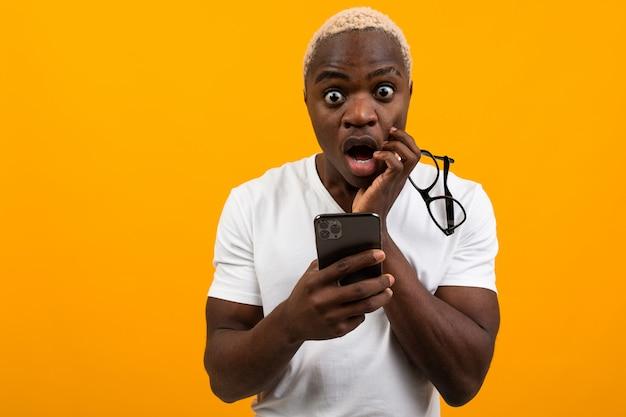 Mooie zwarte amerikaanse student met wit haar kijkt verrast op de telefoon op een gele studio achtergrond