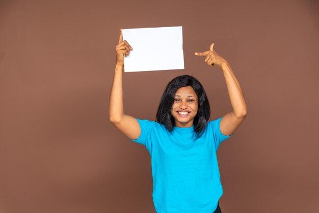 Mooie zwarte dame houdt een leeg bord omhoog en wijst ernaar, ze is blij en heeft een glimlach op haar gezicht