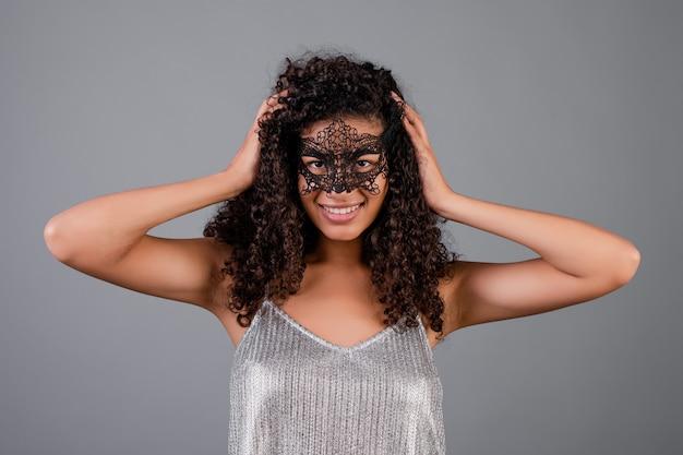 Mooie zwarte die elegant maskerademasker draagt dat over grijs wordt geïsoleerd