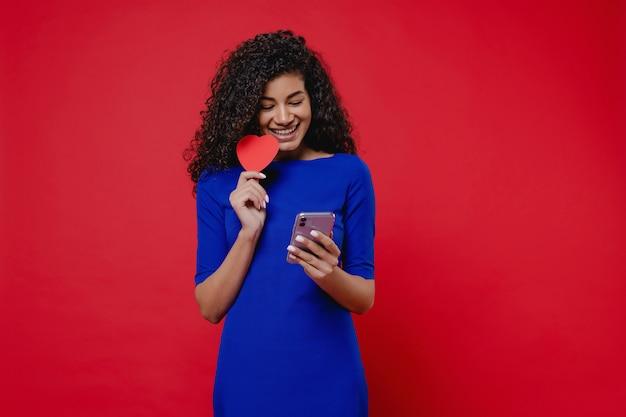 Mooie zwarte die met hart gevormde valentijnskaartkaart op rode muur bekijkt