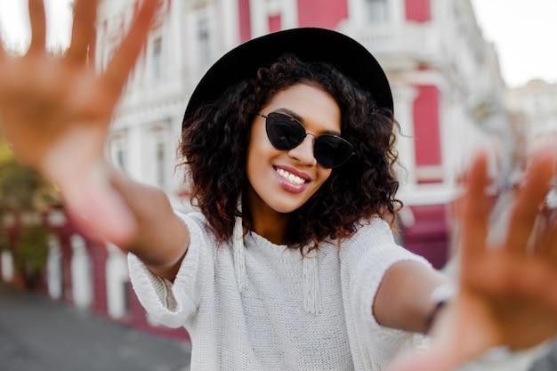 Mooie zwarte die met modieuze afroharen zelfportret maken.