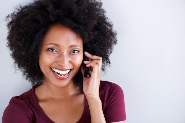 Mooie zwarte die op cellphone en het lachen spreekt