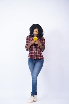 Mooie zwarte die opgewonden haar telefoon bekijkt