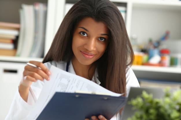Mooie zwarte glimlachende vrouwelijke artsengreep