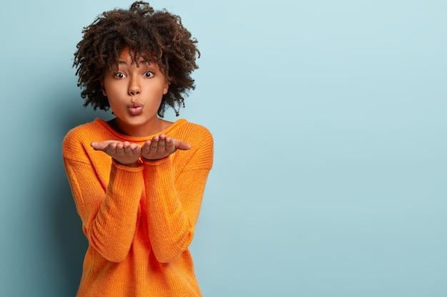 Mooie zwarte meid maakt luchtkus, blaast over twee handpalmen, wil de man kussen, heeft een gezonde huid, draagt een oranje trui, poseert tegen blauwe muur met lege ruimte voor uw promotionele inhoud
