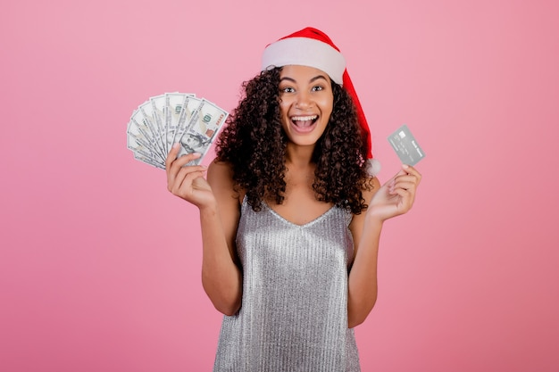 Mooie zwarte met creditcard en contant geld die de hoed van vakantiekerstmis dragen die over roze wordt geïsoleerd
