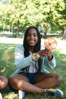 Mooie zwarte tiener die met zeepbellen speelt