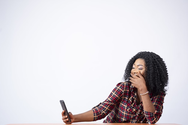 Mooie zwarte vrouw die aan een bureau zit en opgewonden is terwijl ze iets op haar telefoon bekijkt