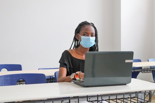 Mooie zwarte vrouw die een masker draagt en bij een computer studeert