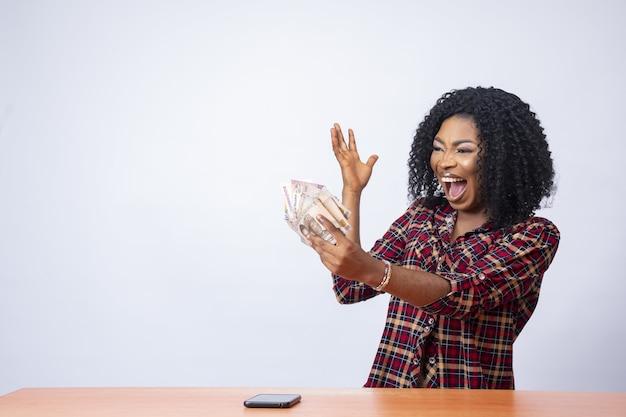 Mooie zwarte vrouw die het geld in haar hand vasthoudt en bekijkt