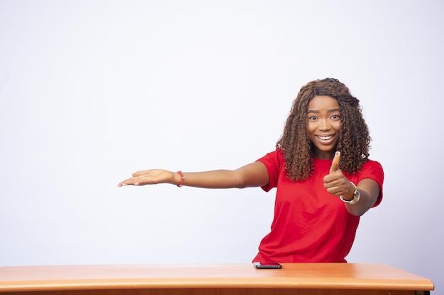 Mooie zwarte vrouw die naar de ruimte aan haar kant wijst en een duim omhoog geeft - reclameconcept