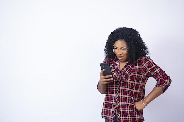 Mooie zwarte vrouw die teleurgesteld naar haar telefoon kijkt