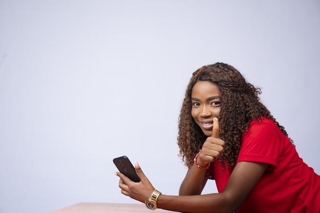 Mooie zwarte vrouw die zijwaarts zit, haar telefoon vasthoudt en een duim omhoog