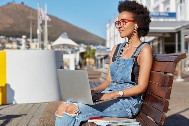 Mooie zwarte vrouw horloges show met oortelefoons en notebook, geniet van een hoog volume, luistert naar audioboek, bereidt zich voor op lessen, wandelt tijdens zonnige zomerdag, draagt jeansoveralls, bladert op internet