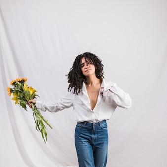 Mooie zwarte vrouw houdt van bloemen boeket