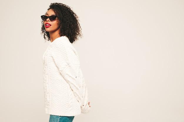 Mooie zwarte vrouw met afro krullen kapsel en rode lippen. glimlachend model in trendy jeans kleding en winter trui.