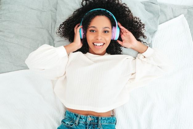 Mooie zwarte vrouw met afro krullen kapsel. glimlachend model in trui en jeans. zorgeloze vrouwelijke luistermuziek in draadloze hoofdtelefoons in de ochtend