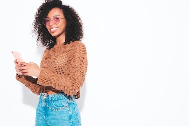 Mooie zwarte vrouw met afro krullen kapsel. glimlachend model in zomerkleren