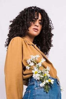 Mooie zwarte vrouw met bloemen in jeans zak