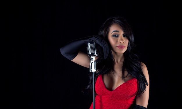 Mooie zwarte zangeres vrouw met retro s microfoon en rode laag uitgesneden jurk