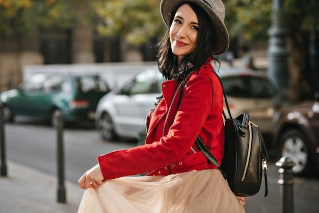 Mooie zwartharige vrouw met verlegen glimlach speelt met rok op straat met auto's aan de muur