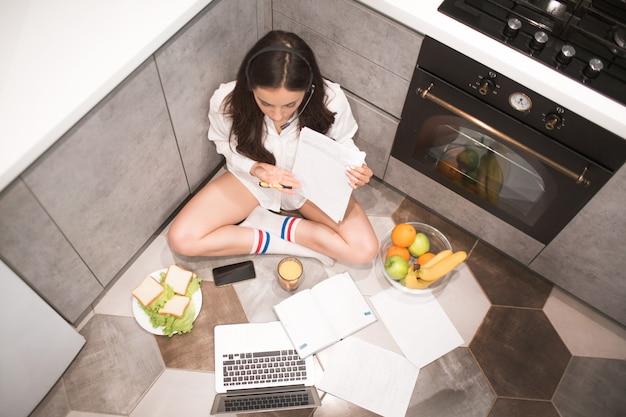 Mooie zwartharige vrouw werkt vanuit huis. een medewerker zit in de keuken en heeft veel werk op een laptop en tablet en heeft videoconferenties en vergaderingen