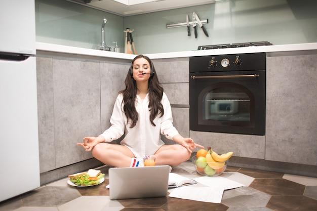 Mooie zwartharige vrouw werkt vanuit huis. een vrouwelijk model zit op de keukenvloer in een yoga-pose. het einde van een evenwichtig en rustig werk.