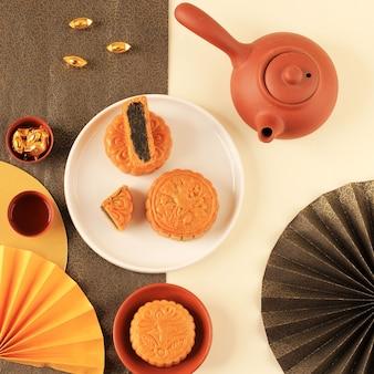 Moon cake chinese dessert snack tijdens het nieuwe maanjaar mid autumn festival. flatlay concept met geel en goud thema. ruimte voor tekst kopiëren