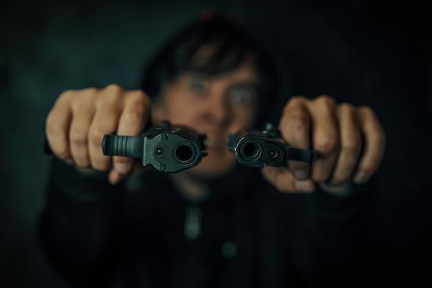 Moordenaar in kap op zwarte achtergrond man dreigt met vuurwapen twee pistolen in mans handen zijn pointe...