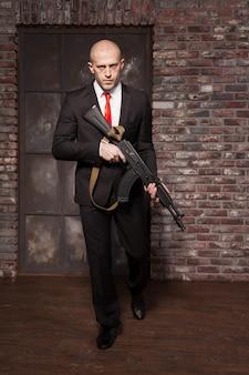 Moordenaar in pak en rode stropdas met machinegeweer