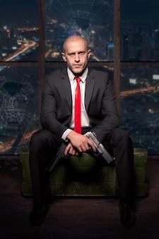 Moordenaar in pak en rode stropdas met pistool in de hand