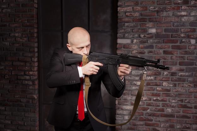 Moordenaar in pak en rode stropdas schiet een machinegeweer
