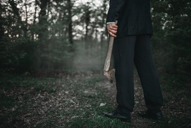 Moordenaar met een bijl in het nachtbos, serieel maniakconcept, misdaad en geweld