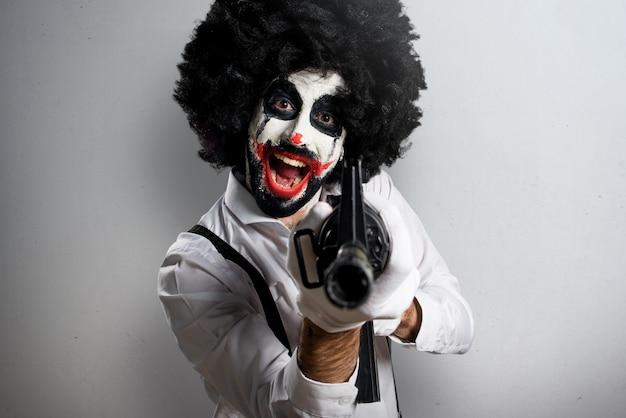 Moordenaarsclown die een geweer op geweven achtergrond houden