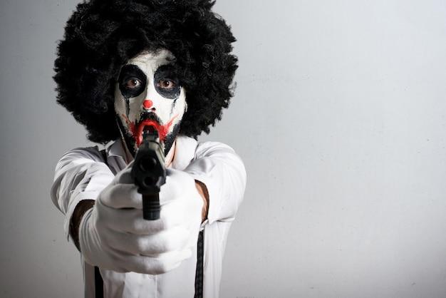 Moordenaarsclown die met een pistool op geweven achtergrond schieten