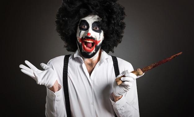 Moordenaarsclown met mes die verrassingsgebaar op geweven rug maken