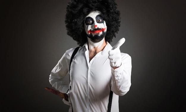 Moordenaarsclown met mes met duim omhoog op geweven achtergrond
