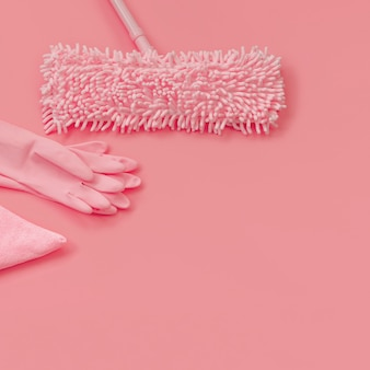 Mop, vod en rubberhandschoenen - roze reeks op roze achtergrond voor de lente het schoonmaken