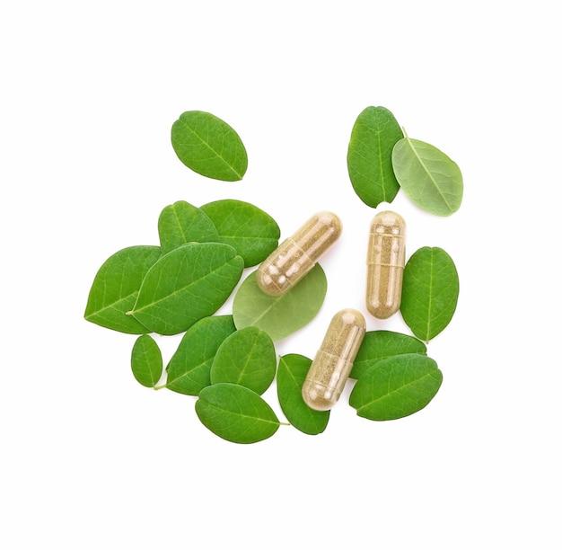 Moringa oleifera capsule met groene verse bladeren op witte achtergrond