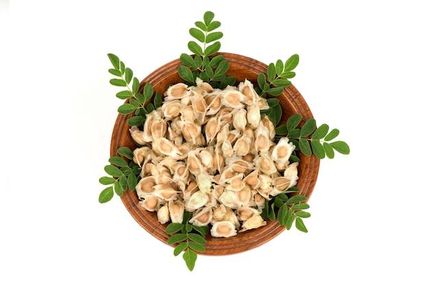Moringa tak groene bladeren en gedroogde zaden geïsoleerd op een witte oppervlakte. bovenaanzicht, plat leggen.